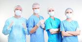 Cirurgiões em pé no fundo cinza — Fotografia Stock