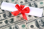 University diploma on dollars background. Cost of education. Conceptual photo. — Stock Photo