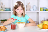 Beautiful little girl eating breakfast in kitchen at home — Stock Photo