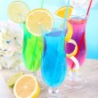 Glasses of cocktails on table on light blue background — Stock Photo