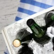 Ice chest full of drinks in bottles on color napkin, on wooden background — Stock Photo #41234945