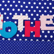 Mother- lettering of handmade paper letters on blue polkbackground — Stock Photo #41235497