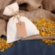 Textile sachet pouch with dried flowers on wooden table, on sackcloth background — Stock Photo #41235593