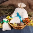 Textile sachet pouches with dried flowers, herbs and berries on wooden table, on sackcloth background — Stock Photo #41235605