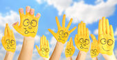 Painted hands with smile on sky background — Stock Photo