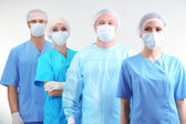 Surgeons standing on grey background — Stock Photo