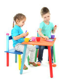 Little children playing with colorful tableware isolated on white — Stock Photo