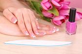 Mãos de mulher bonita com francês manicure e flores sobre fundo de madeira — Foto Stock