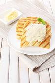 Ahşap masa üzerine tereyağı ile kızarmış ekmek — Stok fotoğraf