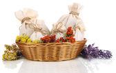 Tekstil poşet torbalar içinde kuru çiçekler, otlar ve üzerinde beyaz izole meyveleri hasır sepet — Stok fotoğraf