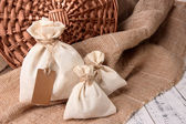 Jute bags on sackcloth, on wooden background — Stock Photo