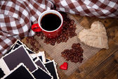 Samenstelling met koffiekopje, decoratieve harten, geruite kruiden en oude foto's in het lege, op houten achtergrond — Stockfoto