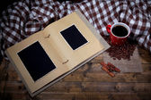 Composition with coffee cup, plaid, and photo album, on wooden background — Zdjęcie stockowe