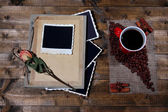 Composition with coffee cup and photo album, on wooden background — Stock Photo