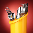 Kitchen cutlery, knives, forks and spoons in yellow stand on red background — Stock Photo #41338611