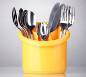 Kitchen cutlery, knives, forks and spoons in yellow stand on grey background — Stock Photo