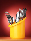 Kitchen cutlery, knives, forks and spoons in yellow stand on red background — Stock Photo