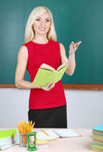 School teacher near table on blackboard background — Stok fotoğraf