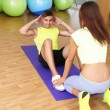 Stock Photo: Guy and trainer engaged in fitness room