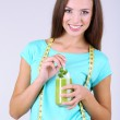 Beautiful girl with fresh juice and measuring tape on grey background — Stock Photo #41341795