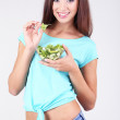 Beautiful girl with fresh salad on grey background — Stock Photo #41341827