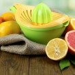 Citrus press and fruits on wooden background — Stock Photo