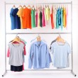 Stock Photo: Different clothes on hangers, on gray background