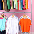 Stock Photo: Different clothes on hangers, on pink background