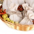 Textile sachet pouches with dried flowers, herbs  and berries  in wicker basket, isolated on white — Stock Photo #41344543