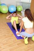 Guy and trainer engaged in fitness room — Stok fotoğraf