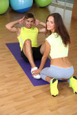 Guy and trainer engaged in fitness room — Стоковое фото