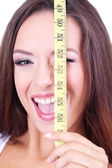 Beautiful young woman with measuring tape close up — Stock Photo