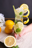 Glass of cocktail with lemon and mint on table on grey background — Stock Photo