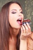 Porträtt av vacker ung flicka med choklad cupcake mot glänsande bakgrund — Stockfoto
