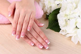 Beautiful woman hands with french manicure and flowers on wooden background — Stockfoto