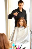 Young man hairdresser do hairstyle girl in beauty salon  — Foto Stock