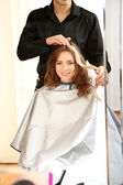 Young man hairdresser dyes hair girl in beauty salon  — Стоковое фото