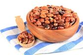 Raw beans in bowl on color napkin, isolated on white — Stock Photo