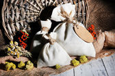 Textile sachet pouch with dried flowers, herbs and berries on wooden table, on sackcloth background — Stok fotoğraf