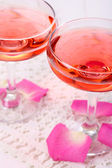 Composition with pink sparkle wine in glasses and rose petals isolated on white — Stock fotografie