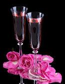 Skład wina różowe okulary i róże na czarnym tle — Zdjęcie stockowe
