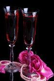 Samenstelling met roze wijn in glazen en rozen geïsoleerd op zwart — Stockfoto