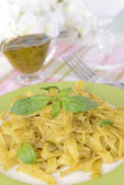 Delicious pasta with pesto on plate on table on light background — Stock fotografie