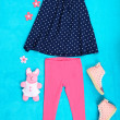 Stock Photo: Beautiful clothes for little girl on blue background