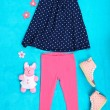 Beautiful clothes for little girl on blue background — Stock Photo #41512239