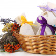 Textile sachet pouches with dried flowers, herbs  and berries  in wicker basket, isolated on white — Stock Photo #41514517