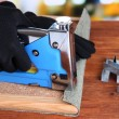 Fastening fabric and board using construction stapler on bright background — Stok Fotoğraf #41515149