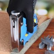 Fastening fabric and board using construction stapler on bright background — Stok Fotoğraf #41515159
