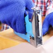 Stock Photo: Fastening fabric and wooden box using construction stapler close up