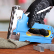 Stock Photo: Fastening fabric and board using construction stapler on bright background